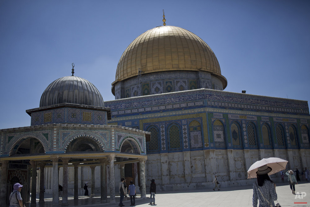 A tourist from Japan holds an umbrella to protect herself from the sun as she walks next to the Golden Dome of the Rock Mosque in the Al Aqsa Mosque compound in Jerusalem's Old City, Wednesday, April 30, 2014. Al Aqsa Mosque compound is one of the holiest site for Muslims. (AP Photo/Ariel Schalit)