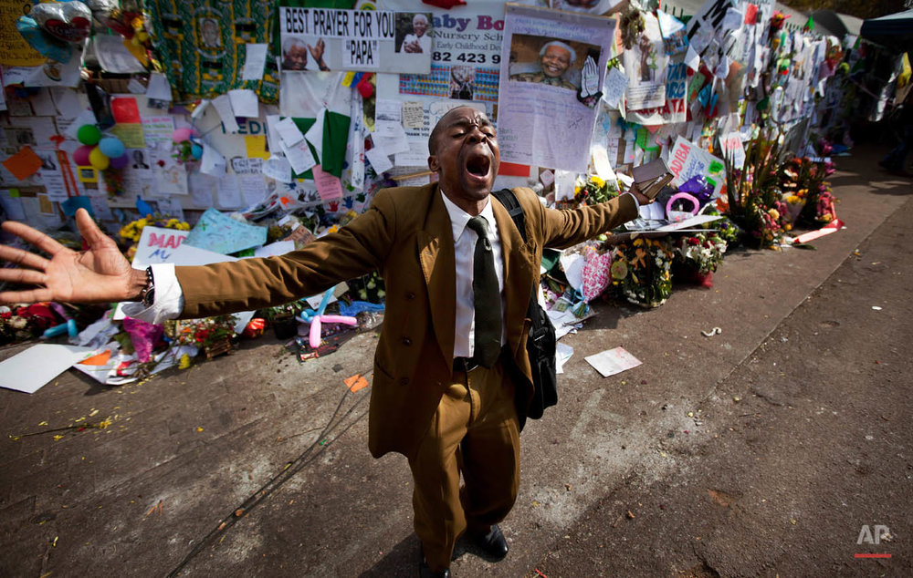 "Gift Mapuka, who described himself as a ""Global Mission Pioneer"" from the Seventh-day Adventist Church, preaches on his own about Jesus and Nelson Mandela, in front of a wall of get-well messages and flowers left by well-wishers, outside the entrance to the Mediclinic Heart Hospital where former South African President Nelson Mandela is being treated in Pretoria, South Africa Friday, July 5, 2013. Mandela, who was hospitalized on June 8, remains in critical but stable condition according to the office of President Jacob Zuma, who visited the anti-apartheid leader on Thursday, and the president's office also said doctors denied reports that 94-year-old Mandela is in a ""vegetative state."" (AP Photo/Ben Curtis)"