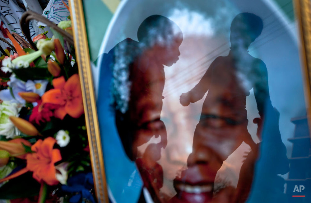 A mother, right, walks to have a family photograph taken with her son, center, seen reflected in a portrait of Nelson Mandela, outside the Mediclinic Heart Hospital where former South African President Nelson Mandela is being treated in Pretoria, South Africa Monday, July 8, 2013. There was no official update Monday morning on the health of the 94-year-old former president and anti-apartheid leader, who was admitted June 8 to the hospital for a recurring lung infection. (AP Photo/Ben Curtis)
