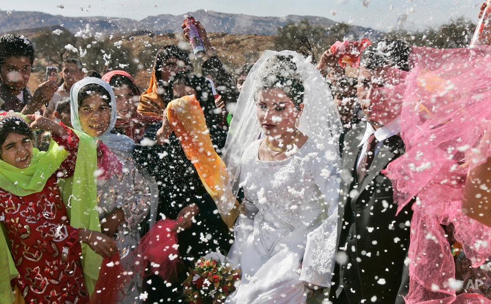 Villagers spray the groom, Mohammed Zamanpour, 25, and his bride Manijeh, 16, with foam confetti at a Bakhtiari nomad wedding in the mountain village of Abid near the town of Masjid-e-Soleiman in southwestern Iran, Thursday, Nov. 29, 2007. Migration has been a way of life for nomads such as the Bakhtiari in Iran for thousands of years but the phenomenon is slowly disappearing as government encroaches and the attractions of urban life draw some away from the nomadic lifestyle. (AP Photo/Ben Curtis)
