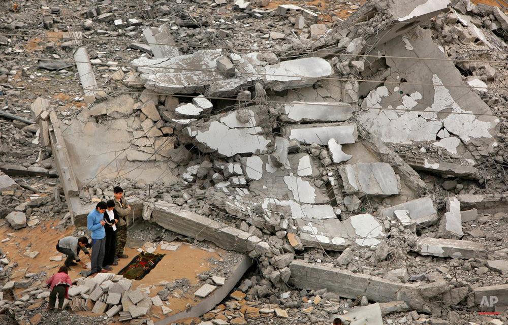 Palestinians offer traditional Muslim Friday prayers amidst the rubble of a destroyed mosque, where only the minaret still stands, in Beit Lahiya in the Gaza strip, Friday, Jan. 23, 2009. Gaza residents headed for Friday communal prayers and Israeli naval guns were largely silent as grief and shock began to mix with a palpable sense of relief in the coastal strip pounded by weeks of Israeli airstrikes and ground assaults. (AP Photo/Ben Curtis)