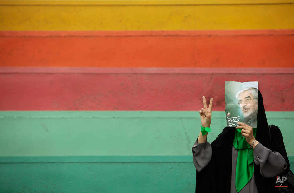A supporter of main challenger and reformist candidate Mir Hossein Mousavi, not wanting to be photographed, hides her face using a poster of him as she waits in the stands at an election rally at the Heidarnia stadium in Tehran, Iran, Tuesday, June 9, 2009. (AP Photo/Ben Curtis)