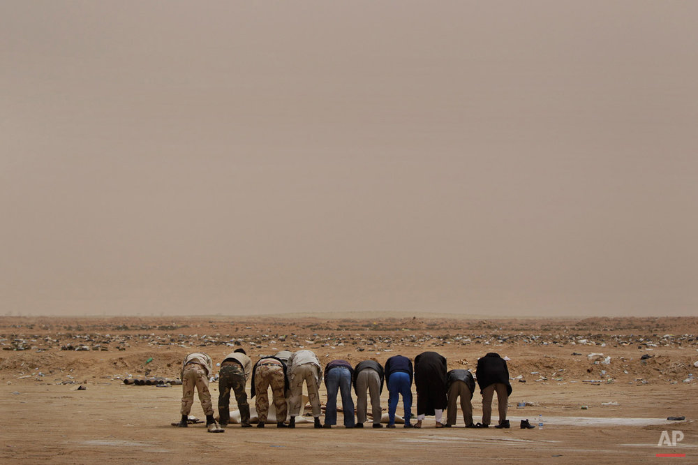 Libyan rebel fighters pray in the desert on hearing claims from other rebels that an airstrike further up the road towards Brega had hit rebel forces killing at least two and injuring more than a dozen, at the west gate of Ajdabiya, Libya Thursday, April 7, 2011. Rebel fighters claimed NATO airstrikes blasted their forces Thursday in another apparent mistake that sharply escalated anger about coordination with the military alliance in efforts to cripple pro-Gadhafi forces. (AP Photo/Ben Curtis)