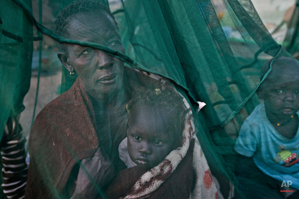 "One of the few to have a mosquito net, a displaced family who fled the recent fighting between government and rebel forces in Bor by boat across the White Nile, sit under it after waking up in the morning in the town of Awerial, South Sudan Thursday, Jan. 2, 2014. The international Red Cross said Wednesday that the road from Bor to the nearby Awerial area ""is lined with thousands of people"" waiting for boats so they could cross the Nile River and that the gathering of displaced is ""is the largest single identified concentration of displaced people in the country so far"". (AP Photo/Ben Curtis)"