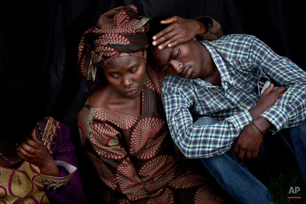 Bizimana Emmanuel, who was born two years before the genocide, is consoled by an unidentified woman while attending a public ceremony to mark the 20th anniversary of the Rwandan genocide, at Amahoro stadium in Kigali, Rwanda Monday, April 7, 2014. Sorrowful wails and uncontrollable sobs resounded Monday as thousands of Rwandans packed the country's main sports stadium to mark the 20th anniversary of the beginning of a devastating 100-day genocide. (AP Photo/Ben Curtis)