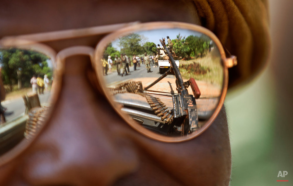 "A Chadian soldier wearing reflective sunglasses observes the convoy ahead of him, as Chadian soldiers who are fighting in support of Central African Republic president Francois Bozize, ride on the road leading to Damara, about 70km (44 miles) north of the capital Bangui, Central African Republic Wednesday, Jan. 2, 2013. More than 30 truckloads of troops from Chad line the two-lane highway just outside of Damara, supporting government forces who want to block a new rebel coalition from reaching the capital, and Gen. Jean Felix Akaga, who heads a 10-nation regional force, says the town is a ""red line that the rebels cannot cross"" or his forces will attack. (AP Photo/Ben Curtis)"