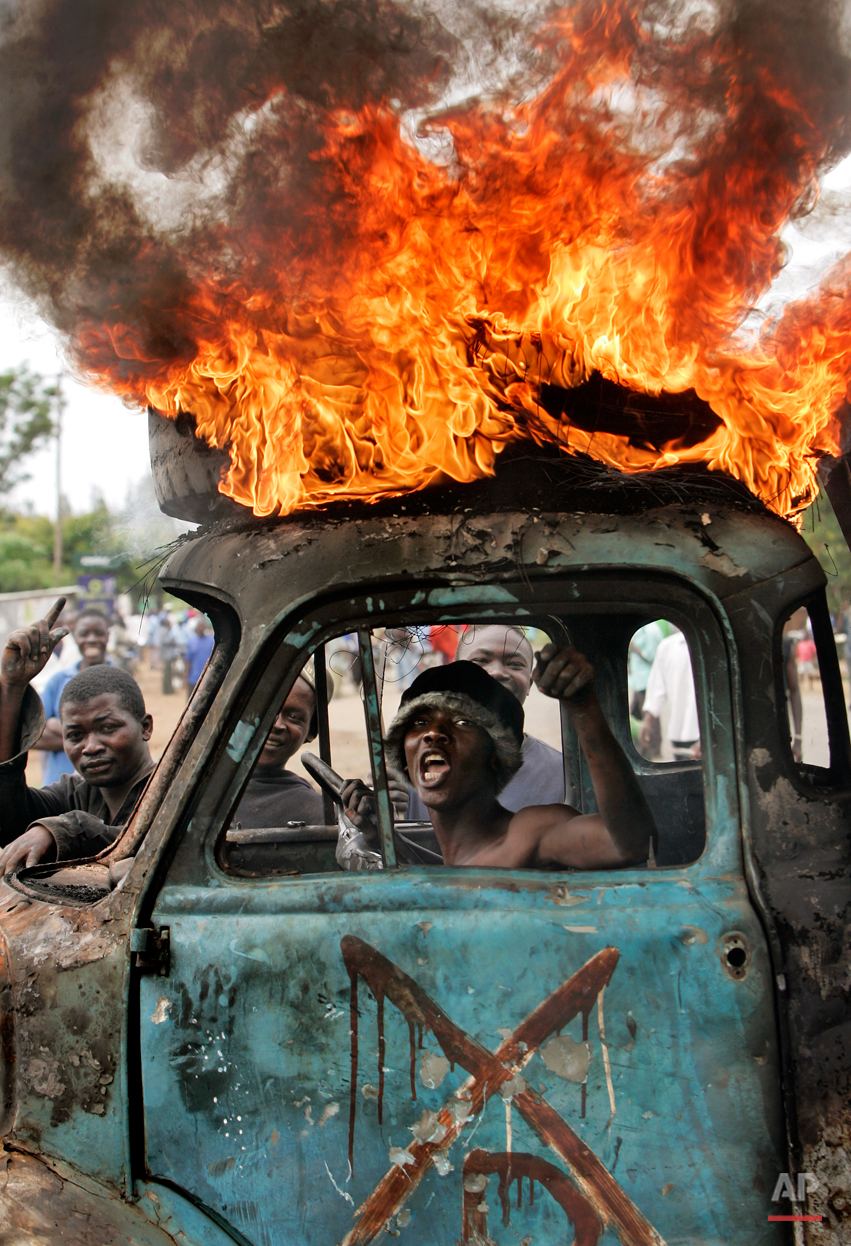 A Kenyan man sits in the cab of a destroyed truck used as a makeshift roadblock while a tyre burns on the roof, as he and others enforce the roadblock in Kisumu, Kenya, Tuesday, Jan. 29, 2008. The town of Kisumu is now almost completely ethnically cleansed of Kikuyus, and mobs armed with makeshift weapons erect burning roadblocks and search for the few Kikuyu targets remaining. (AP Photo/Ben Curtis)
