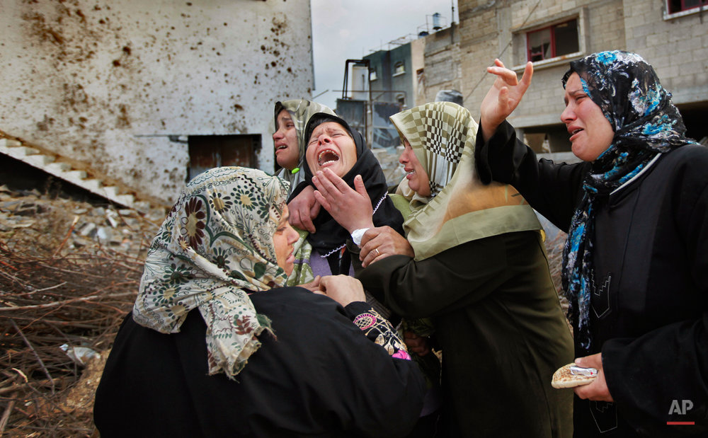 A Palestinian woman from the Suboh family weeps as she is comforted after learning the body of a releative was dug out of the rubble of a house destroyed in recent days in Israeli bombardment in Beit Lahiya, northern Gaza strip, Monday, Jan. 19, 2009. The bodies of four Hamas fighters from the same family,  Bassem, Nashad, Sharif, and Rizek Suboh,  were pulled from the rubble in the are that was hit hard in an Israeli miltary offensive.  Israel hopes to pull all its troops out of the Gaza Strip by the time Barack Obama is inaugurated as president of the United States on Tuesday, Israeli officials  (AP Photo/Ben Curtis)
