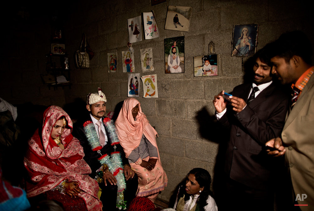 """In this Saturday, Feb. 7, 2015 photo, Pakistani Christian bride Dunya Yacob, 24, and her groom Indriaz Liaqat, 27, sit during their wedding ceremony in a makeshift home at a slum home to Christian families on the outskirts of Islamabad, Pakistan. ìSince I was a little girl, I dreamed of the day I would get married and put on a nice dress and have a nice party with a lot of people,î the 24 year old said. """"But today, my dream didn't turn the way I imagined it, but there is nothing I can do about it. This is how our lives look like today and we have to adapt."""" (AP Photo/Muhammed Muheisen)"""