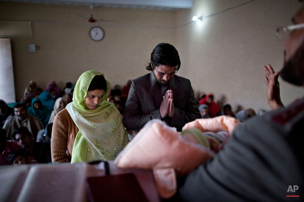 In this Sunday, Feb. 8, 2015 photo, Pakistani Christian Shanaz Rafiq, 28, left, and her husband Rashid Rafiq, 32, stand in front of a pastor during the baptism ceremony of their son, at the Salvation Army Church in Rawalpindi, Pakistan. In this country of 180 million people, where Islam is the state religion and 95 percent of people are Muslims, Christians represent just a sliver of the population. (AP Photo/Muhammed Muheisen)