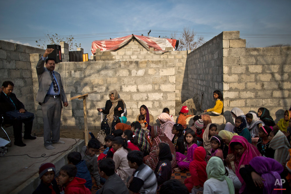 In this Sunday, Feb. 8, 2015 photo, Pakistani Christians pray during Sunday Mass in a makeshift church in a slum home to Christian families on the outskirts of Islamabad, Pakistan. The colony home to many Christians who once lived elsewhere in the capital, but fled in fear after a string of blasphemy allegations and killings. In this country of 180 million people, where Islam is the state religion and 95 percent of people are Muslims, Christians represent just a sliver of the population. (AP Photo/Muhammed Muheisen)
