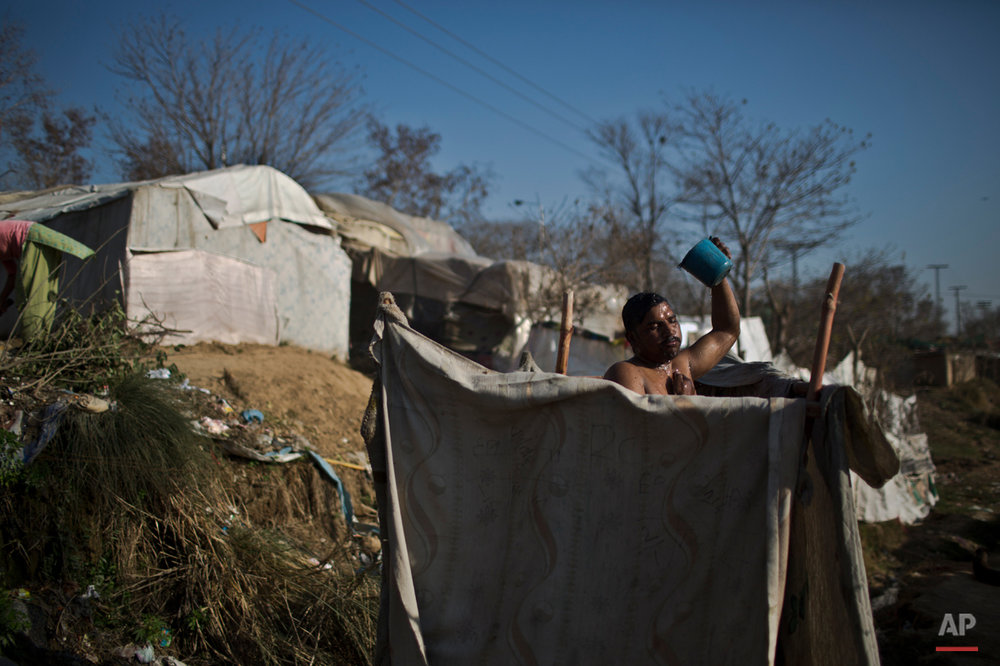In this Wednesday, Feb. 4, 2015 photo, Pakistani Christian Arshad Massi, 33, showers in a makeshift bathroom in a slum home to Christian families on the outskirts of Islamabad, Pakistan. Many of the Christians living in this slum have once lived elsewhere in the capital, but fled in fear after a string of blasphemy allegations and killings. In this country of 180 million people, where Islam is the state religion and 95 percent of people are Muslims, Christians represent just a sliver of the population. (AP Photo/Muhammed Muheisen)