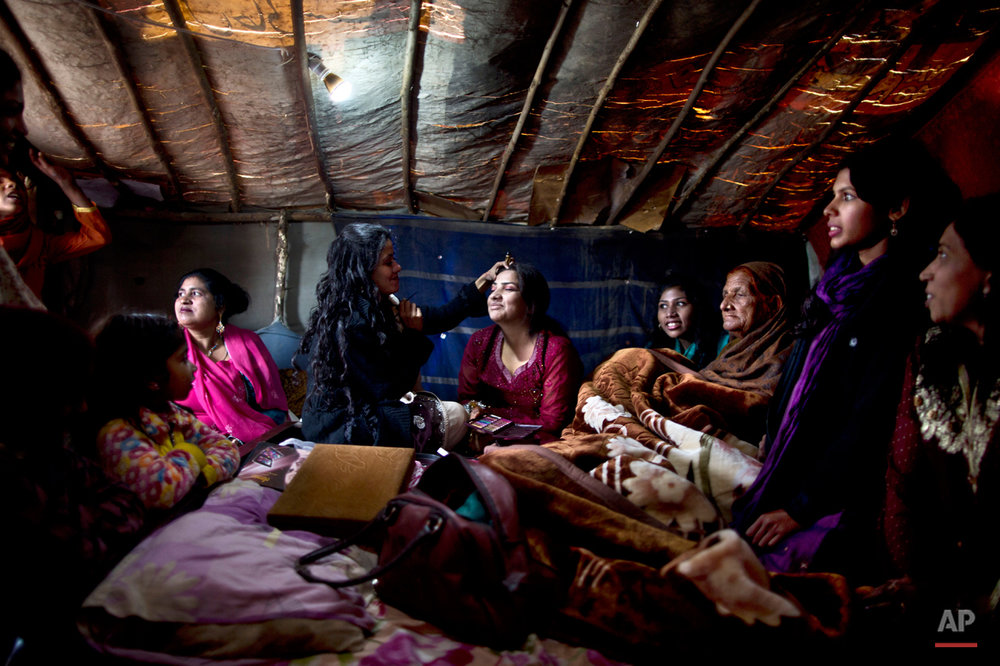 In this Saturday, Feb. 7, 2015 photo, Pakistani Christian bride Dunya Yacob, 24, center, surrounded by family members while having her makeup done on her wedding day in a makeshift tent at a slum home to Christian families on the outskirts of Islamabad, Pakistan. ìSince I was a little girl, I dreamed of the day I would get married and put on a nice dress and have a nice party with a lot of people,î the 24 year old said. ìBut today, my dream didnít turn the way I imagined it, but there is nothing I can do about it. This is how our lives look like today and we have to adapt.î (AP Photo/Muhammed Muheisen)