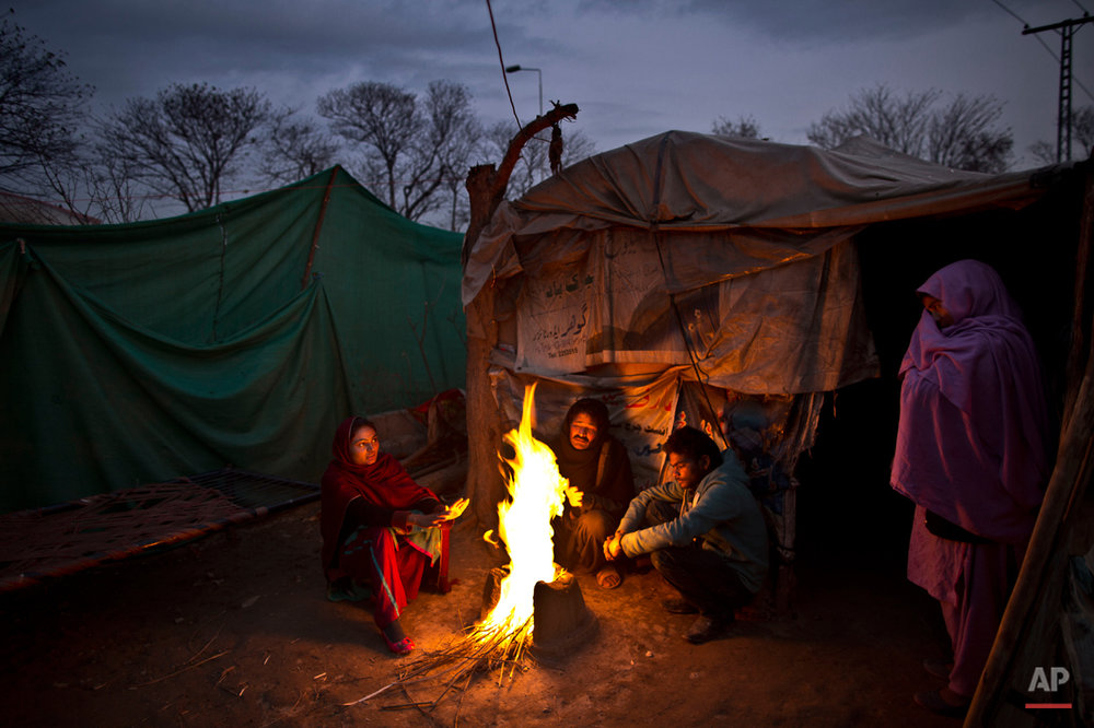 In this Tuesday, Feb. 3, 2015 photo, Pakistani Christian Basharat Bhatti, 43, center, sits with his family gathering around a fire to warm themselves from the evening cold, outside their makeshift tent at a slum home to Christian families on the outskirts Islamabad, Pakistan. The colony home to many Christians who once lived elsewhere in the capital, but fled in fear after a string of blasphemy allegations and killings. In this country of 180 million people, where Islam is the state religion and 95 percent of people are Muslims, Christians represent just a sliver of the population. (AP Photo/Muhammed Muheisen)