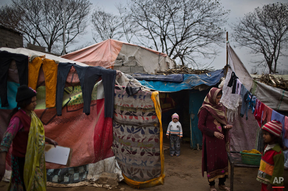 In this Monday, Feb. 2, 2015 photo, Pakistani Christians hang their laundry outside their makeshift tent in a slum home to Christian families on the outskirts of Islamabad, Pakistan. In this country of 180 million people, where Islam is the state religion and 95 percent of people are Muslims, Christians represent just a sliver of the population. (AP Photo/Muhammed Muheisen)