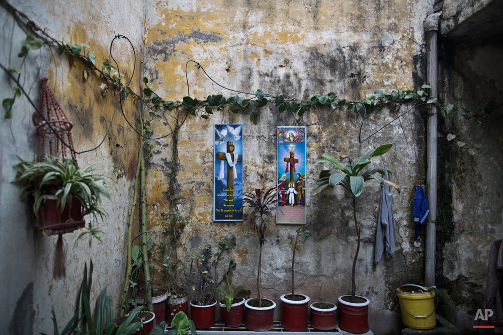 In this Sunday, Feb. 1, 2015 photo, biblical pictures are hung on a wall of Pakistani Christian Rashid Rafiq's home in Rawalpindi, Pakistan. In this country of 180 million people, where Islam is the state religion and 95 percent of people are Muslims, Christians represent just a sliver of the population. (AP Photo/Muhammed Muheisen)