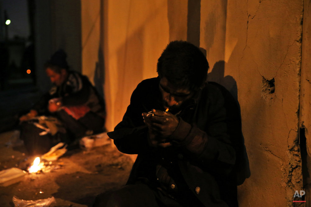 In this Wednesday, Feb. 4, 2015 photo, an addict uses crystal meth in a street in midnight in Tehran, Iran. Anti-narcotics and medical officials say more than 2.2 million of Iran's 80 million citizens already are addicted to illegal drugs, including 1.3 million on registered treatment programs. (AP Photo/Ebrahim Noroozi)