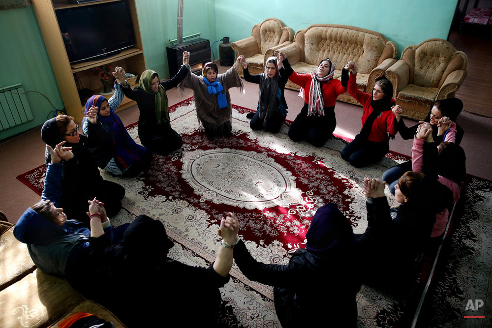 In this Monday, Feb. 2, 2015 photo, female drug addicts pray in their dorm, at Chitgar treatment camp, in a mountain village northwest of Tehran, Iran. Anti-narcotics and medical officials say more than 2.2 million of Iran's 80 million citizens already are addicted to illegal drugs, including 1.3 million on registered treatment programs. (AP Photo/Ebrahim Noroozi)