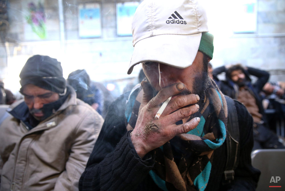 In this Tuesday, Feb. 3, 2015 photo, a drug addict smokes cigarette at drop-in center and shelter south of Tehran, Iran. Anti-narcotics and medical officials say more than 2.2 million of Iran's 80 million citizens already are addicted to illegal drugs, including 1.3 million on registered treatment programs. (AP Photo/Ebrahim Noroozi)