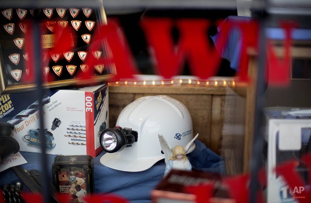 In this Oct. 18, 2014 photo, a coal miner's hard hat and lamp sit in the window  of a downtown pawn shop in Harlan, Ky. Mine employment in Kentucky is at its lowest levels since the Great Depression. As recently as the late 1970s, there were more than 350 mines operating at any given time in Harlan County. Today, it's around 40. (AP Photo/David Goldman)