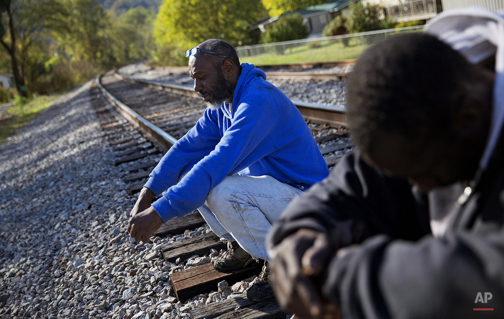 "In this Oct. 19, 2014 photo, unemployed coal miner Steven Fields, 50, left, sits on the railroad tracks near his home in Coxton, Ky. Fields was laid off from his coal mining job five years ago and plans to leave his family behind to look for work in Alabama. ""There just ain't nothing for me to do here,"" says Fields. ""I figured I got about ten years left to work, I'm fighting for those ten years."" (AP Photo/David Goldman)"