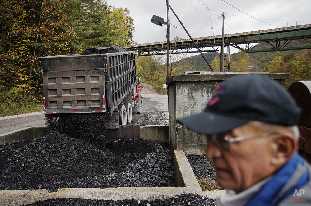 "In this Oct. 15, 2014 photo, coal mine owner C.V. Bennett III, stands by as a truck dumps coal into a pit at his processing plant in Cumberland, Ky. The Bennetts have been running mines in Harlan County for 102 years. But unless the government backs off considerably, he's not sure they'll last another five. ""We're living everyday but we're dying everyday too,"" says Bennett. (AP Photo/David Goldman)"