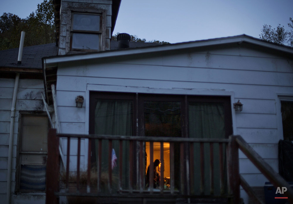 "In this Oct. 19, 2014 photo, unemployed coal miner Steven Fields, 49, stands in the bedroom of his home at dusk in Coxton, Ky. Fields was laid off from his coal mining job five years ago and plans to leave his family behind to look for work in Alabama. ""It's a hard pill to swallow when you're laying at home and your wife's supporting you, instead of you supporting your wife,"" he says, huffing and coughing. (AP Photo/David Goldman)"