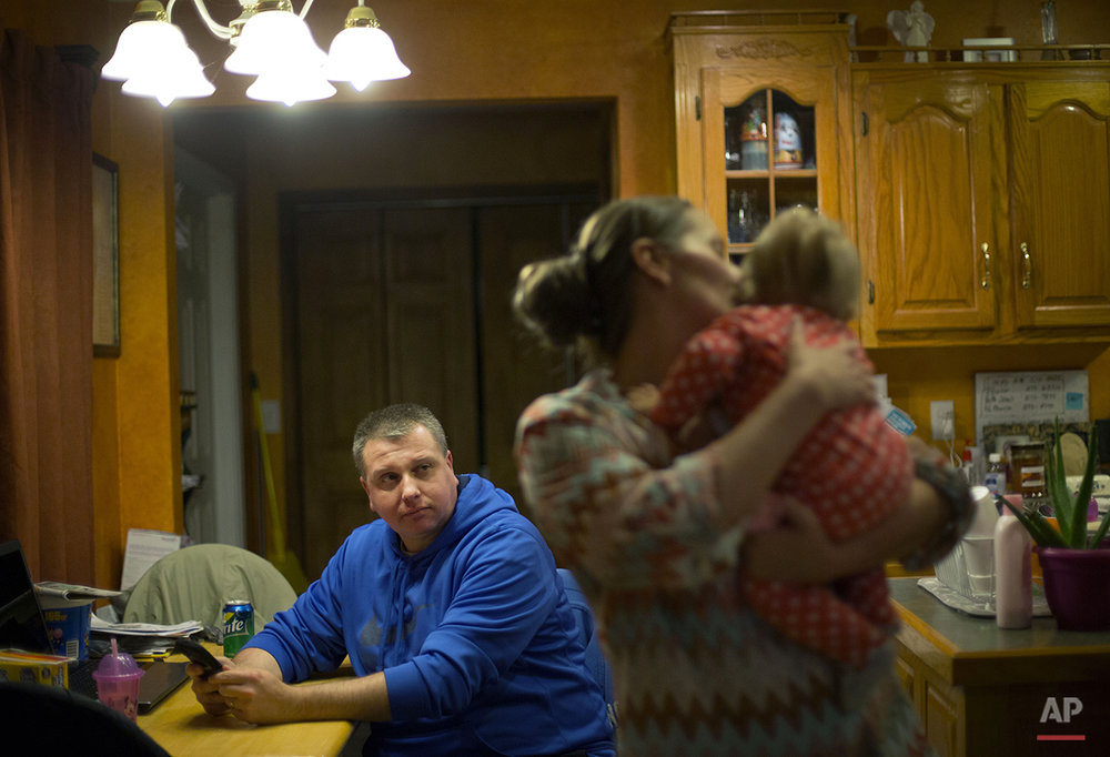 In this Oct. 18, 2014 photo, Scottie Sizemore sits at the kitchen table as his wife Madonna holds their daughter Anastyn, 10 mo, at their home in Harlan, Ky. After Sizemore's company announced they were slashing salaries 7 and a half percent and not long after that another 7 percent cut was coming, he decided to leave the mountains his family has called home for at least four generations and take a job coal mining in Western Kentucky. Since commuting home on weekends, Sizemore is hoping to pack up their home in Harlan and have the family back under one roof out west. (AP Photo/David Goldman)