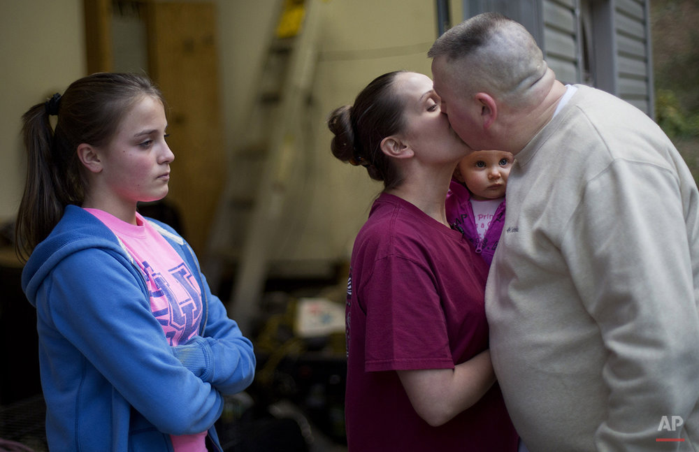 In this Oct. 20, 2014 photo, Madonna Sizemore says goodbye to her husband Scottie, right, as he leaves to return to his job working at a coal mine some five hours away in western Kentucky after spending the weekend at home with 10-month-old daughter Anastyn, center right, and stepdaughter Bryannah Ramsey, 14, in Harlan, Ky. Scottie plans to move the family out west but Madonna said that she hates to leave her beloved mountains. (AP Photo/David Goldman)