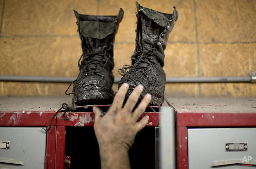 In this Oct. 15, 2014 photo, coal miner Johnny Turner, 35, puts his coal boots on top of his locker after finishing a shift underground at the Perkins Branch coal mine in Cumberland, Ky. Since January 2012, the state has lost more than 7,000 direct mining jobs, some of the most lucrative in this part of the country. Mine employment in Kentucky is at its lowest levels since the Great Depression. (AP Photo/David Goldman)