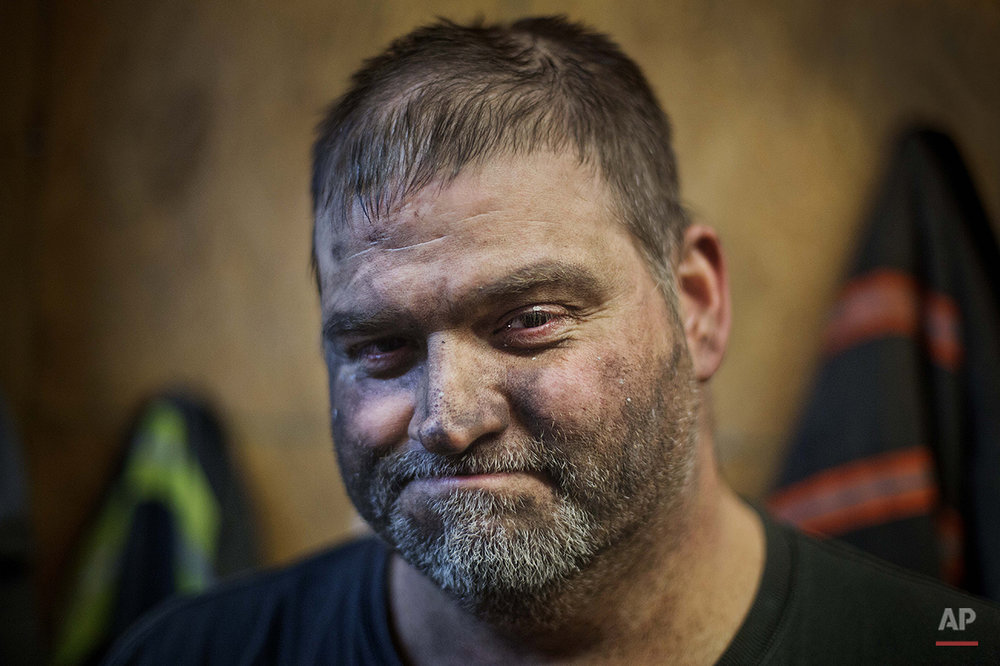In this Oct. 15, 2014 photo, twenty-six year coal mine veteran Mike Pennington, 45, poses for a photo in the locker room after working a shift underground in the Perkins Branch coal mine in Cumberland, Ky. Since January 2012, the state has lost more than 7,000 direct mining jobs, some of the most lucrative in this part of the country. Mine employment in Kentucky is at its lowest levels since the Great Depression. (AP Photo/David Goldman)