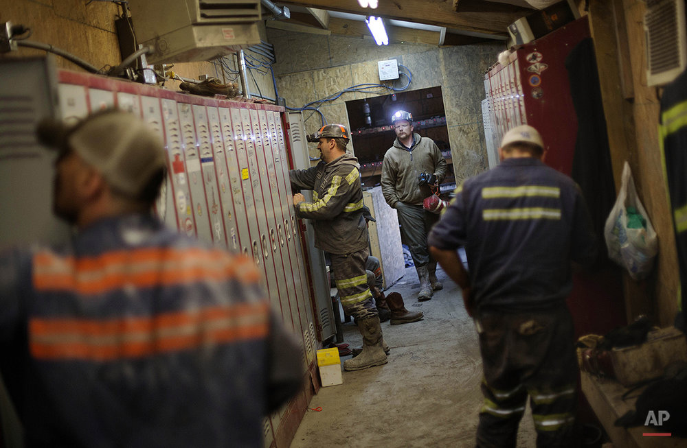 "In this Oct. 15, 2014 photo, coal miners change in a locker room after working a shift underground at the Perkins Branch Coal Mine in Cumberland, Ky. Most of what's still being mined in Harlan County is ""met coal"" _ the high-grade metallurgical coal used to make coke for steel production. As long-term contracts to supply ""steam"" coal to power companies expire, the mines that produced it are being shuttered. (AP Photo/David Goldman)"