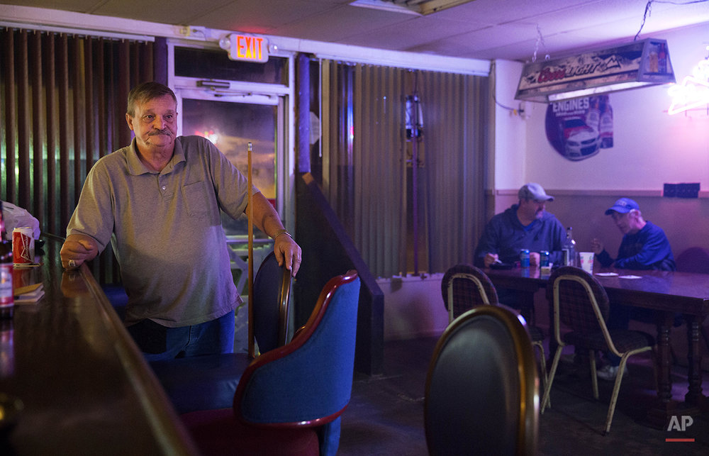 "In this Oct. 19, 2014 photo, former coal miner Tommy Walters, 66, waits his turn while playing pool in his bar, one of only two still operating in the area in Cumberland, Ky. Walters, a 17-year coal mine veteran, had left home numerous times over the years looking for work out of state as the opportunities for coal miners at home fluctuated. ""It bothers you, it hurts you that one time this town was booming,"" said Walters. ""If I knew back then what this town would be like today, I never would have come back."" (AP Photo/David Goldman)"