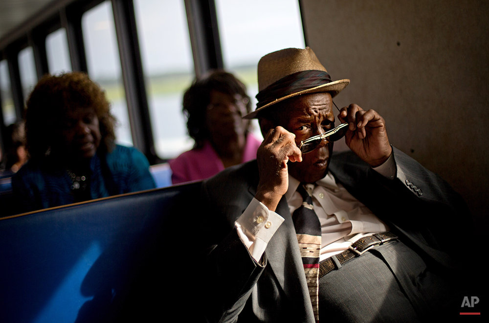 Eddie Wilson, 65, puts on his glasses while riding the ferry from the mainland to attend a church service for the 129th anniversary of St. Luke Baptist Church on Sapelo Island, Ga. on Sunday, June 9, 2013. Isolated over time to the Southeast's barrier islands, the Geechee of Georgia and Florida, otherwise known as Gullah in the Carolinas, have retained their African traditions more than other African American communities in the U.S. (AP Photo/David Goldman)