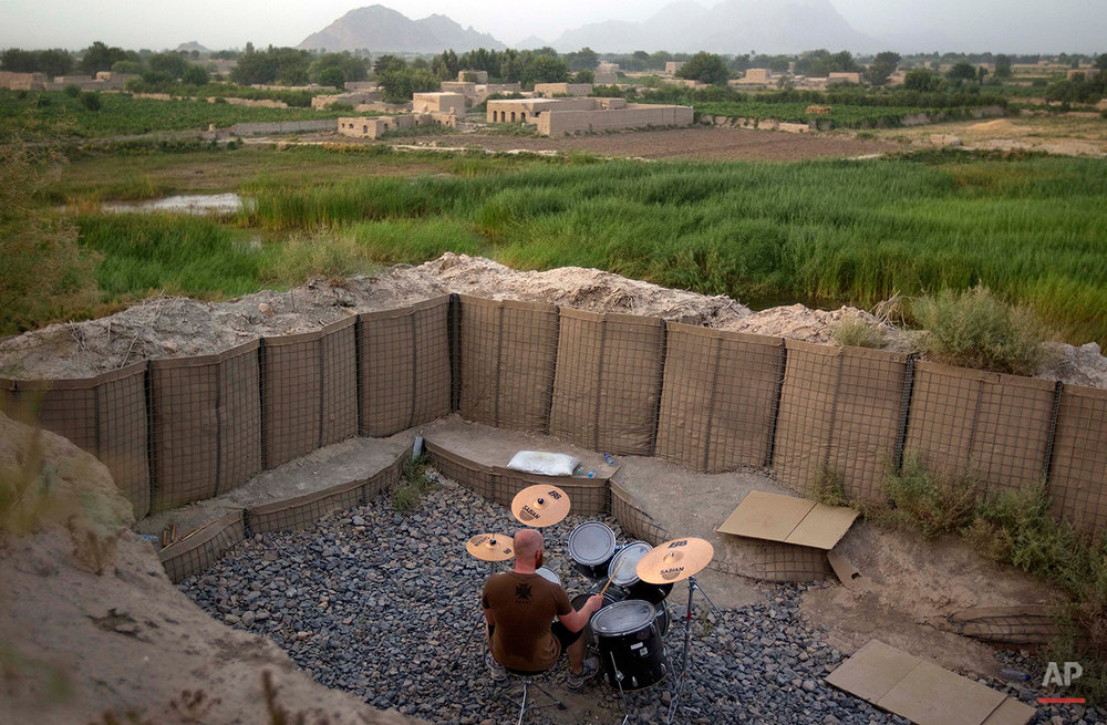 Canadian Forces soldier, Cpl. Ben Vandandaigue, plays on a drum kit, Friday, June 24, 2011, on Forward Operating Base Sperwan Ghar overlooking the Panjwaii district of Kandahar province, Afghanistan. (AP Photo/David Goldman)