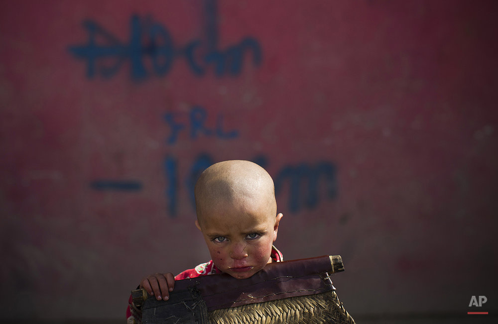 An Afghan child sit next to the shop of his father in the old city of Kabul, Afghanistan, Saturday, March 3, 2012. (AP Photo/Anja Niedringhaus)