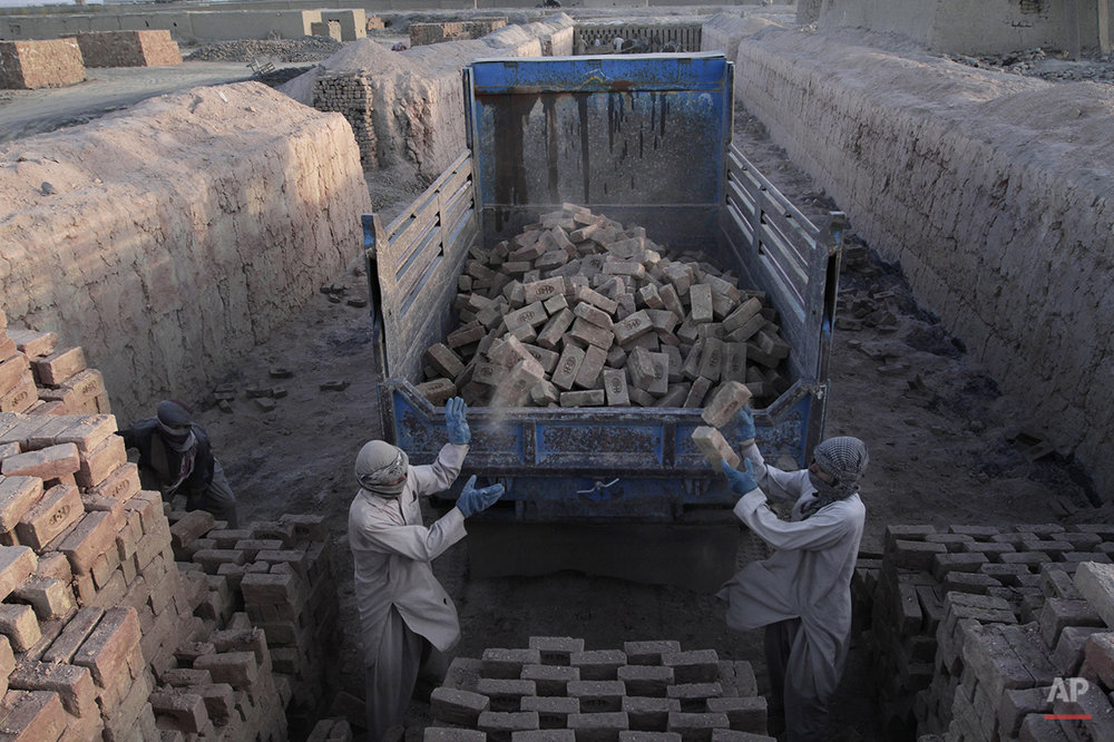 Mohammed Osman, 28, center, and Mohammad Anwar, 25, throw bricks onto a truck at a brick factory on the outskirts of Kabul, Afghanistan, Sunday, Oct. 27, 2013. Men generally work for 12 hours a day, six days a week, and make about 557.980 Afghani ($10) per day. (AP Photo/Rahmat Gul)