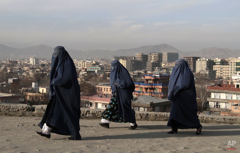 Afghan women walk along on the street in Kabul, Afghanistan, Friday, Dec. 20, 2013. (AP Photo/Rahmat Gul)