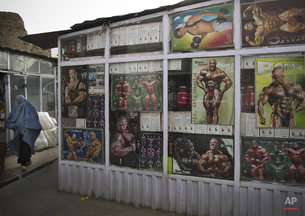An Afghan woman walks past a bodybuilders shop in the old town of Kabul, Afghanistan, Sunday, April 7, 2013. (AP Photo/Anja Niedringhaus)
