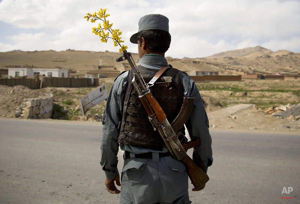 An Afghan National Police officer mans a checkpoint on the outskirts of Maidan Shahr, Wardak province, Wednesday, May 15, 2013. The National Police and Army are providing security unaided by international troops now in most of Afghanistan. (AP Photo/Anja Niedringhaus)