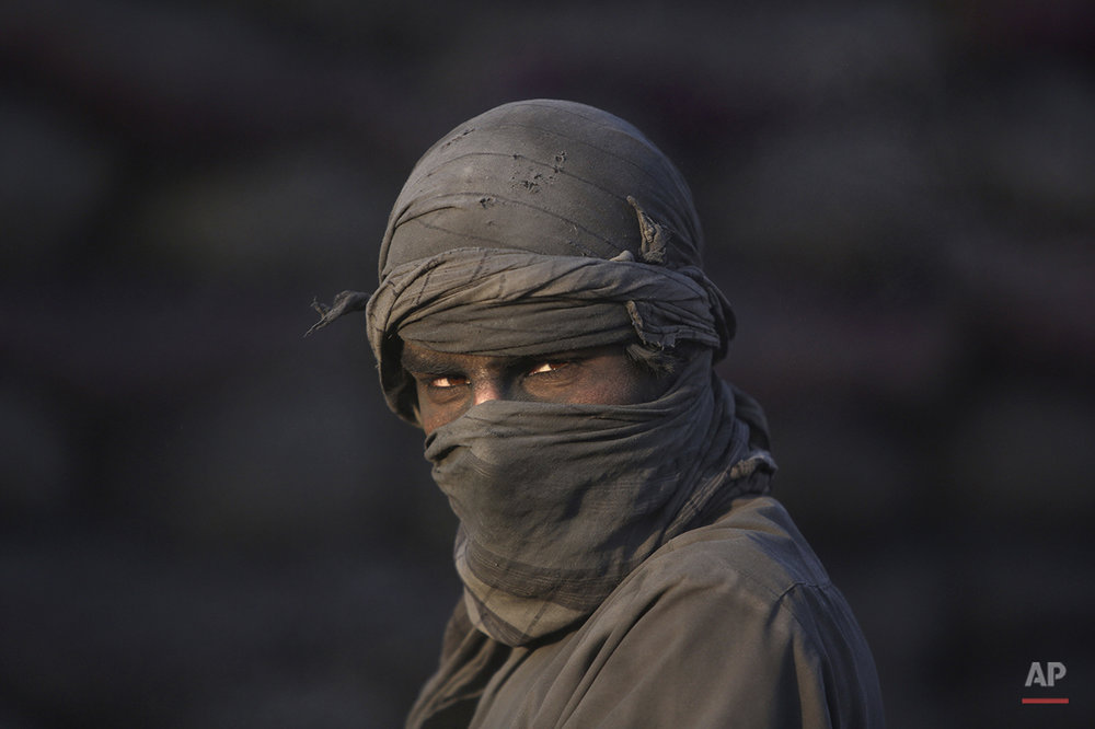 An Afghan laborer pauses as he works at a charcoal shop on the outskirts of Kabul, Afghanistan, Wednesday, Nov. 26, 2014. In the winter, prices of wood and charcoal rise among all other necessities for Afghans. (AP Photo/Rahmat Gul)