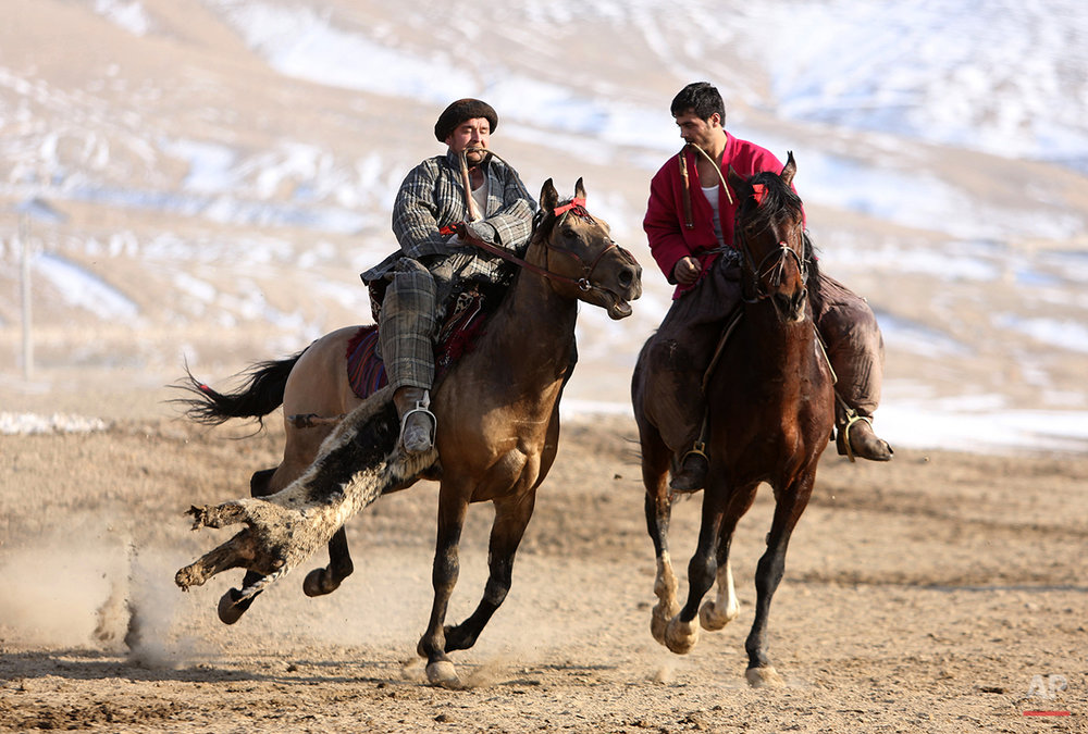 "Afghan horse riders play ""buzkashi"" game during a friendly match on the outskierts of Kabul, Afghanistan, Tuesday, Jan. 14, 2014. Buzkashi is the national sport of Afghanistan, in which players fight to place a goat carcass into a circle goal. (AP Photo/Rahmat Gul)"