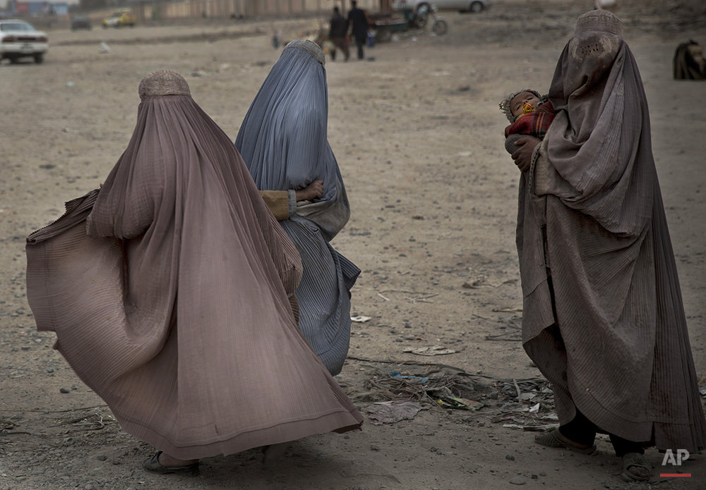 Afghan women beg in the street for money in the center of Kandahar, Afghanistan, Wednesday, March 12, 2014. Kandahar, the capital of the province with the same name, is the birthplace of the hard-line Islamic militant movement that held power in the country for five years until it was ousted in a 2001 U.S.-led invasion following the Sept. 11 terror attacks in the United States.  (AP Photo/Anja Niedringhaus)