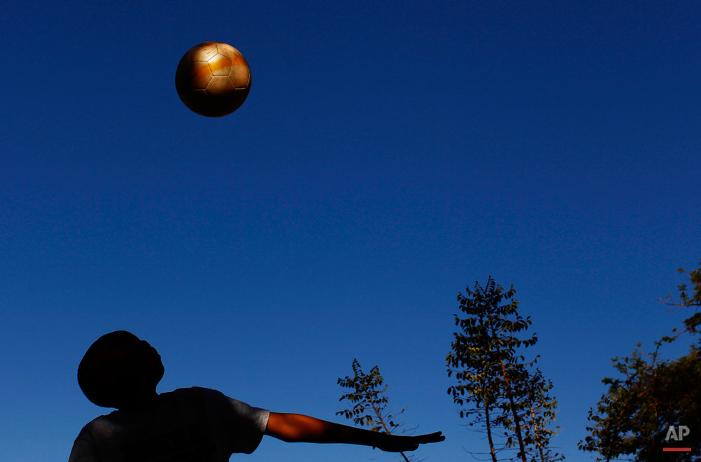 A youth plays with a soccer ball before the World Cup group F soccer match between Italy and New Zealand at Mbombela Stadium in Nelspruit, South Africa, Sunday, June 20, 2010.  (AP Photo/Bernat Armangue)