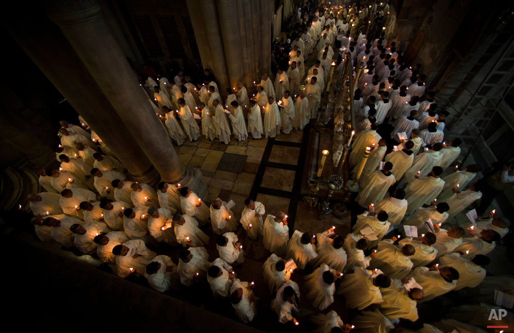 Catholic clergy walk holding candles during the Holy Thursday procession of the Washing of the Feet inside the Church of the Holy Sepulchre, traditionally believed to be the burial site of Jesus Christ, in Jerusalem's Old City, Thursday, April 5, 2012. (AP Photo/Bernat Armangue)