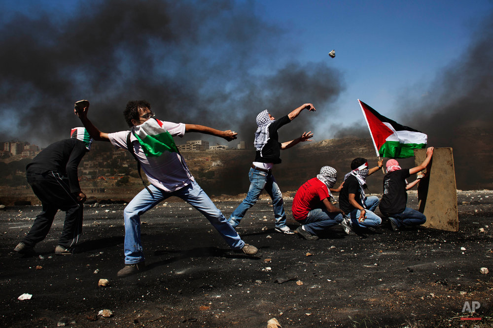 "Masked Palestinians hurl stones at Israeli troops, not seen, during clashes outside the Ofer military prison, near the West Bank city of Ramallah, Tuesday, May 15, 2012 during the 64th anniversary of ""Nakba"", Arabic for catastrophe, the term used to mark the events leading to Israel's founding in 1948. Hundreds of thousands of Palestinians fled or were forced from their villages during the war over Israel's 1948 creation, an event they commemorate every year as their ""Nakba"". (AP Photo/Bernat Armangue)"