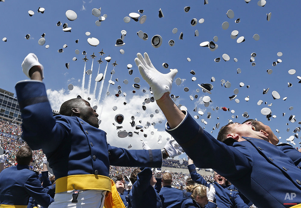 Air Force Academy graduates throw their caps into the air as F-16 jets from the Thunderbirds make a flyover, at the completion of the graduation ceremony for the class of 2014, at the U.S. Air Force Academy, in Colorado, Wednesday, May 28, 2014.  (AP Photo/Brennan Linsley)