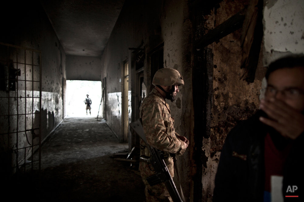 A Pakistani army officer, walks in a corridor riddled with bullet marks, as a man, right, covers his nose form the smell of the blood, inside the Army Public School attacked last Tuesday by Taliban gunmen, in Peshawar, Pakistan, Thursday, Dec. 18, 2014. The Taliban massacre that killed more than 140 people, mostly children, at a military-run school in northwestern Pakistan left a scene of heart-wrenching devastation, pools of blood and young lives snuffed out as the nation mourned and mass funerals for the victims got underway. (AP Photo/Muhammed Muheisen)