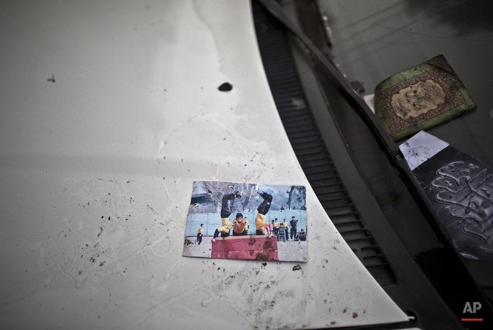 A picture showing schoolchildren playing is left on a car, inside the Army Public School attacked last Tuesday by Taliban gunmen, in Peshawar, Pakistan, Thursday, Dec. 18, 2014. The Taliban massacre that killed more than 140 people, mostly children, at a military-run school in northwestern Pakistan left a scene of heart-wrenching devastation, pools of blood and young lives snuffed out as the nation mourned and mass funerals for the victims got underway. (AP Photo/Muhammed Muheisen)