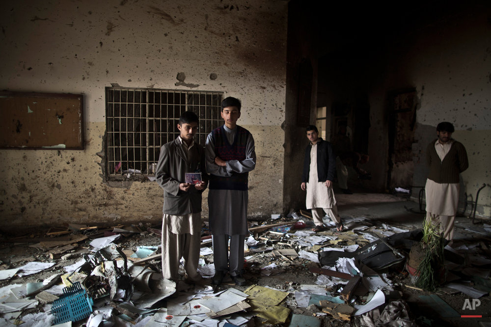 Pakistani students, Waqar Ahmad, left, and Uwais Naser, who survived last Tuesday's Taliban attack on a military-run school, stand at the site, one holding a picture of their headmaster Tahira Kazi, 58, who was killed in the attack, in Peshawar, Pakistan, Thursday, Dec. 18, 2014. The Taliban massacre that killed more than 140 people, mostly children, at a military-run school in northwestern Pakistan left a scene of heart-wrenching devastation, pools of blood and young lives snuffed out as the nation mourned and mass funerals for the victims got underway. (AP Photo/Muhammed Muheisen)